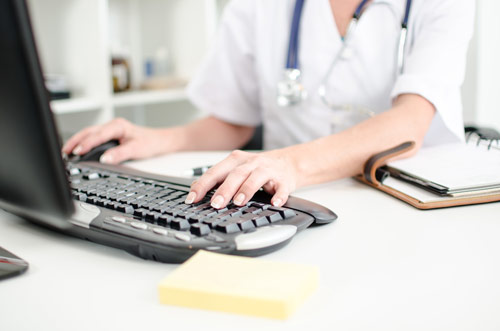 Doctor at Computer Inputing Patient Data