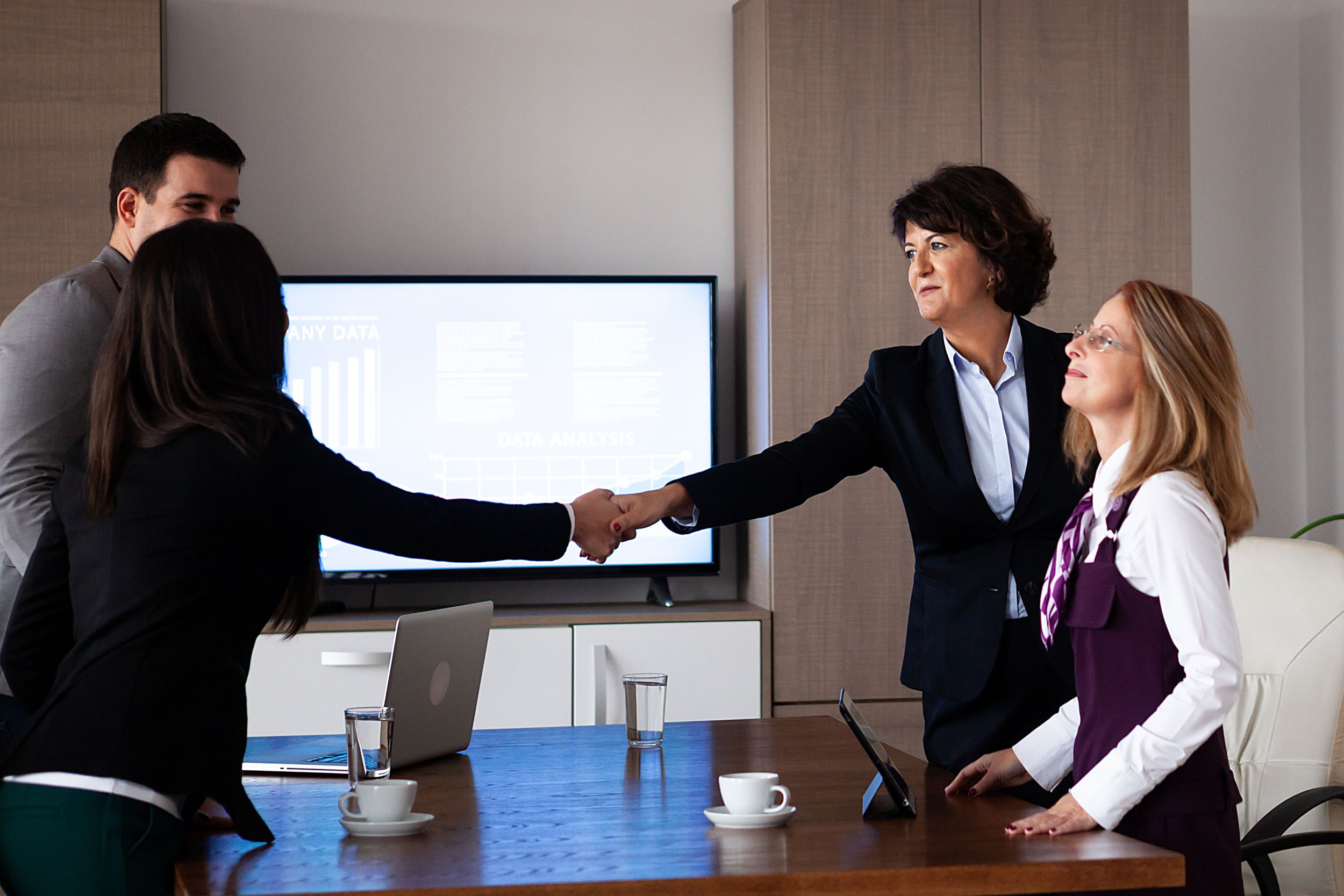 a few executives pictured shaking hands in a boardroom meeting