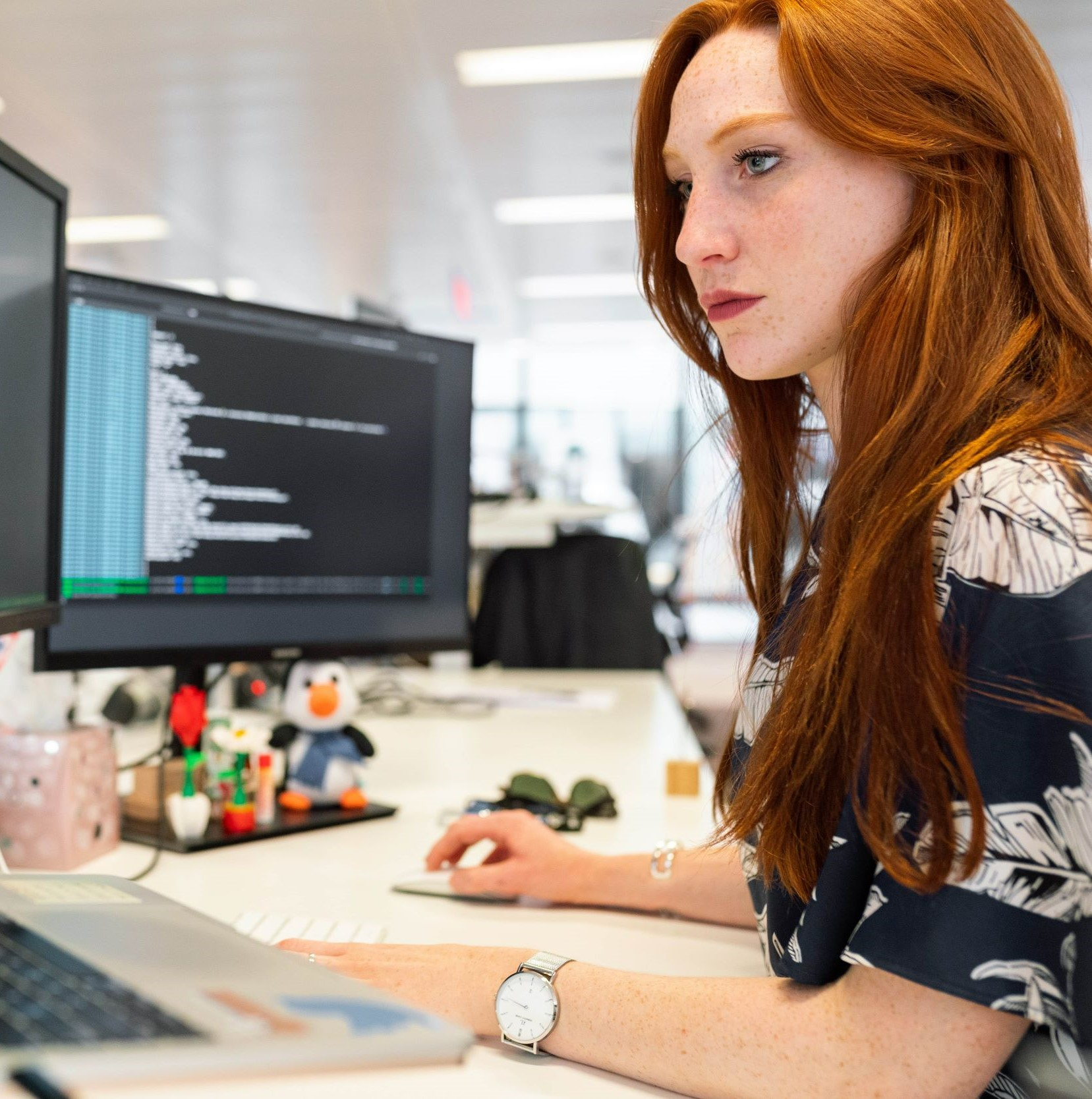 young professional shown coding at a desk